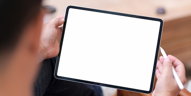 Man using blank screen tablet in comfortable room Premium Photo