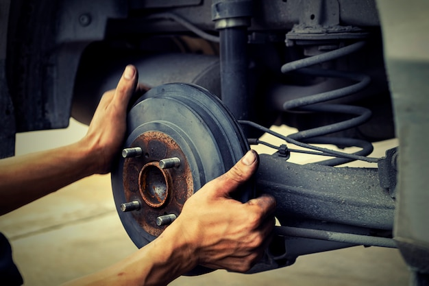 Man using car mechanic block the wind wheel.     to check your tires and brake for car.auto mechanic preparing for the work. Premium Photo