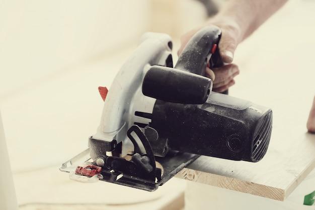 Человек с помощью электрической пилы в столярной мастерской Бесплатные Фотографии