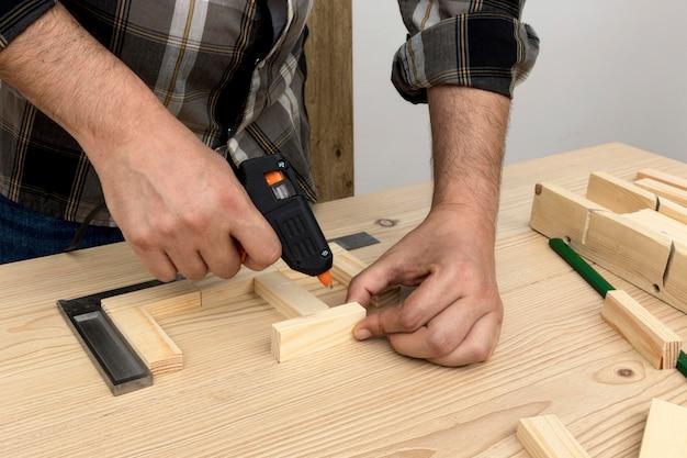 Man using glue on wood carpentry workshop concept Free Photo