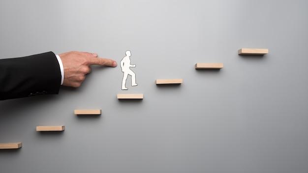Man using his finger pushing paper human figure Premium Photo