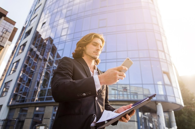 Man using his phone on a sunny morning Free Photo
