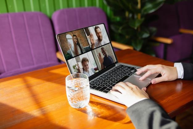 Человек, использующий ноутбук для видеозвонка, пьет воду Бесплатные Фотографии
