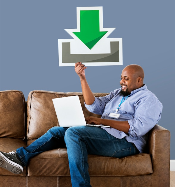 Man using a laptop and holding a download icon Free Photo