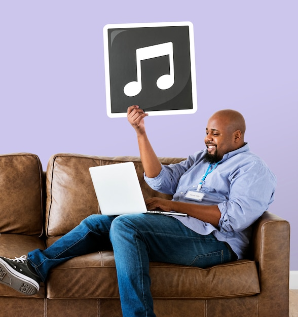 Man using a laptop and holding a musical note Free Photo