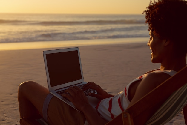Man using laptop while relaxing in a beach chair on the beach Free Photo