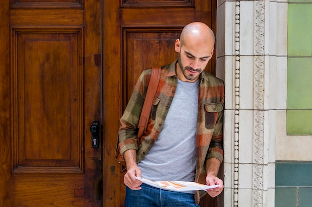 Man using map to orientate in city Free Photo