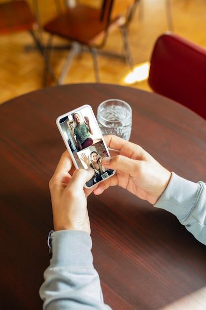 Человек использует мобильный телефон для видеозвонка, попивая воду Бесплатные Фотографии