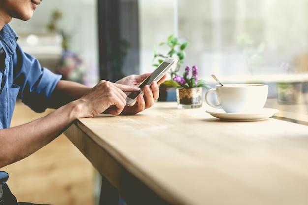 コーヒーショップでモバイルスマートフォンを使用している男。 Premium写真