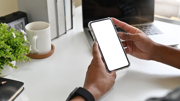 Man using mockup mobile phone on office desk with clipping path display. Premium Photo