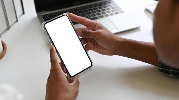 Человек используя мобильный телефон модель-макета на столе офиса с дисплеем пути клиппирования. Premium Фотографии