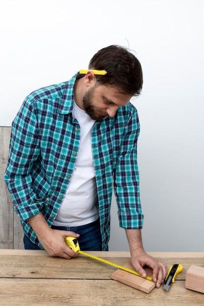 Man using ruler and wood carpentry workshop concept Free Photo