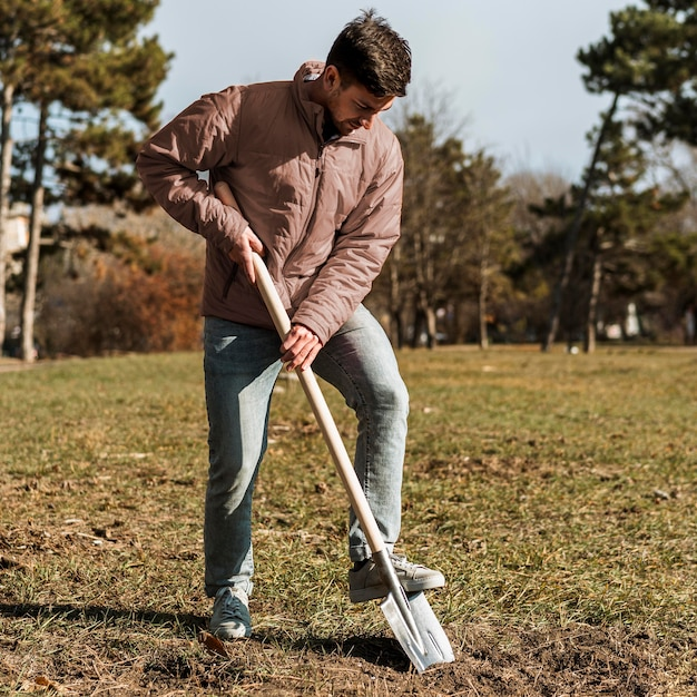 Man using shovel to dig a hole for planting a tree Free Photo