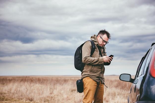Человек с помощью смарт-телефона на открытом воздухе Premium Фотографии