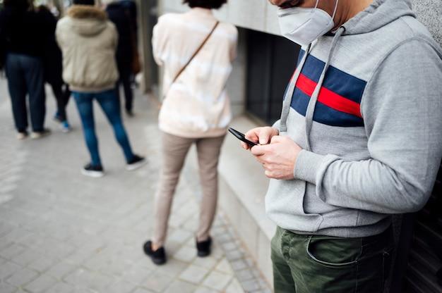 Человек с помощью смартфона в ряд людей, ожидающих Premium Фотографии