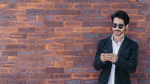 Man using smartphone near brick wall Free Photo