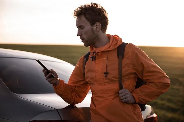 Uomo che utilizza smartphone all'aperto durante un viaggio su strada Foto Gratuite
