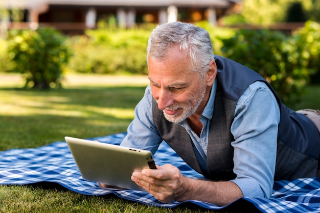 Man using a tablet outside medium shot Free Photo