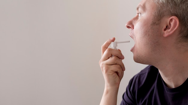 Man usingtreatment for sore throat copy space Free Photo