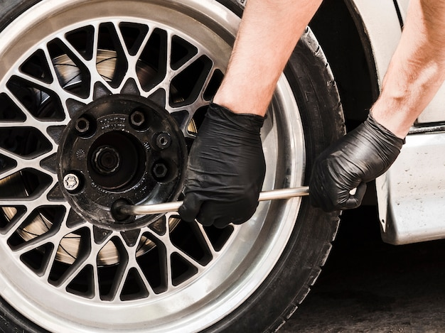 Man using a wrench to tighten wheel nuts Free Photo