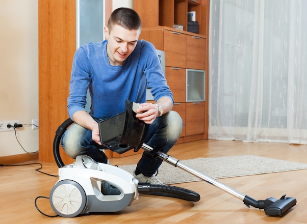 Man  vacuuming with vacuum cleaner on parquet floor in living room Free Photo