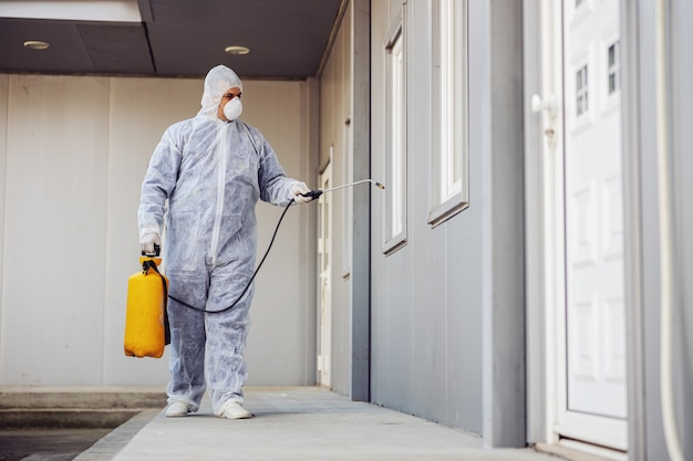 Man in virus protective suit and mask disinfecting buildings of coronavirus with the sprayer. infection prevention and control of epidemic. world pandemic. Premium Photo