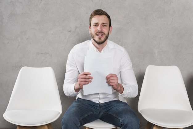 Man waiting for his job interview and holding resume Premium Photo