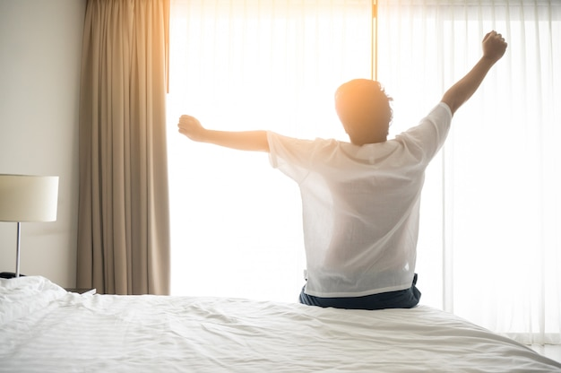 Man wake up and stretching in morning with sunlight Premium Photo