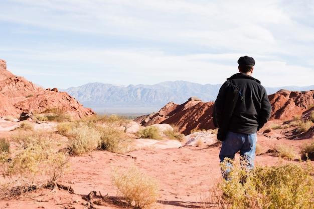 Man walking in desert landscape Free Photo