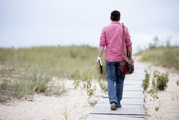 Человек идет по деревянной дорожке, несёт свою сумку и держит библию Бесплатные Фотографии