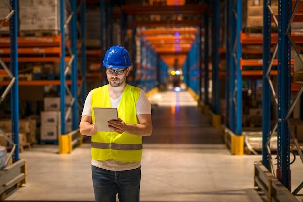大規模な倉庫保管倉庫センターを歩き、タブレットを使用して流通を制御する男性 無料写真