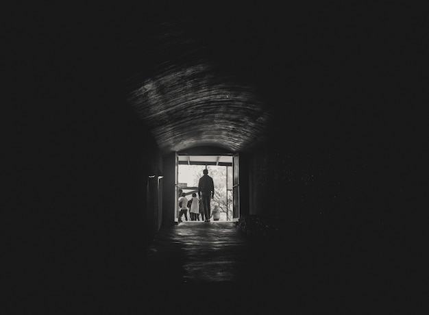 Man walking toward the light at the end of a tunnel Free Photo
