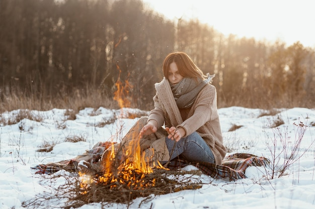 Uomo in fase di riscaldamento accanto a un falò in inverno Foto Gratuite