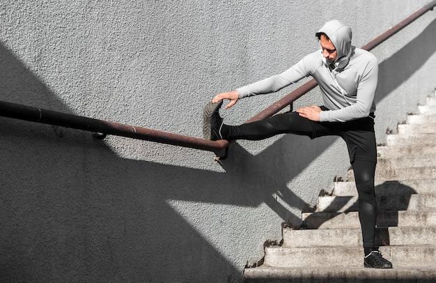 Man warming up his legs using a railing Free Photo