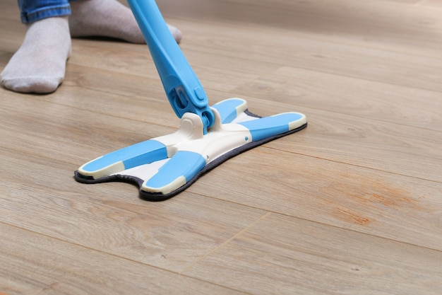 A man washes the floors with a mop in room. under the bed. cleaning. Premium Photo