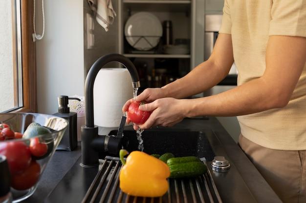 男は台所の流しで野菜を洗う Premium写真