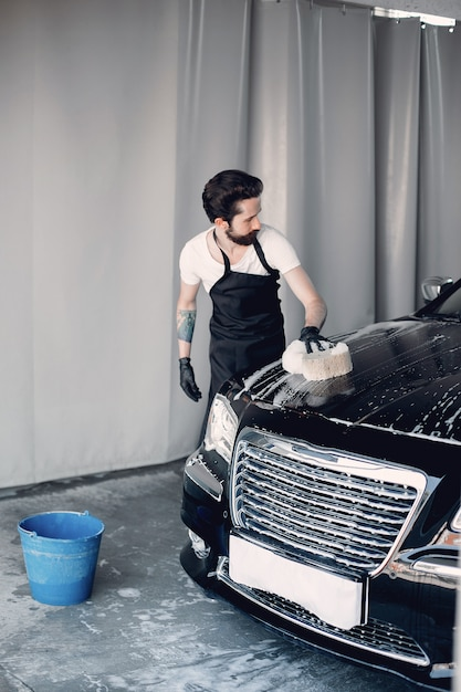 Man washing his car in a garage Free Photo