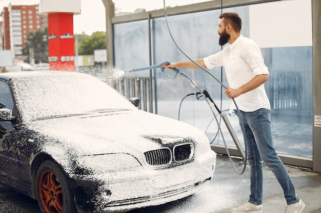 Man washing his car in a washing station Free Photo