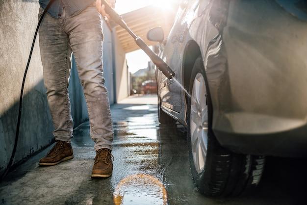 Man washing his car with pressure washer Premium Photo
