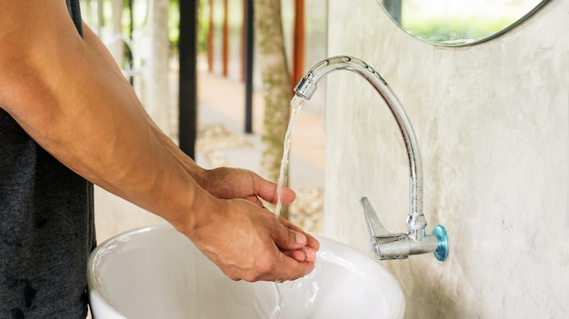 Man washing his hands in the basin. Premium Photo