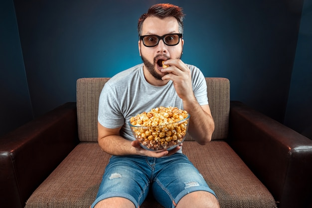 A man watches a movie or series with 3d glasses, a blue wall. the concept of a cinema, films, emotions, surprise, leisure, streaming platforms. Premium Photo