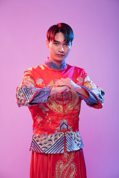 Un uomo che indossa cheongsam è in piedi e rispetta i clienti che vengono a fare acquisti nel capodanno cinese Foto Gratuite