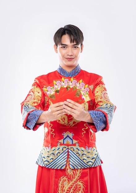 L'uomo che indossa cheongsam è molto fortunato a ricevere soldi in regalo dai genitori nella giornata tradizionale Foto Gratuite