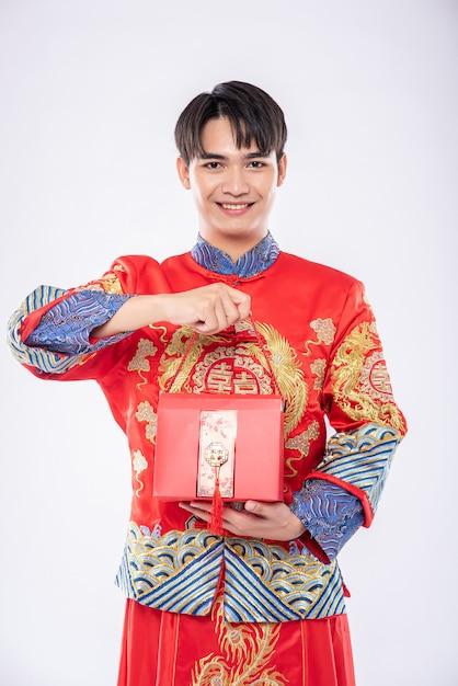 L'uomo indossa cheongsam pronto a dare la borsa rossa alla sorella per sorprendere nella giornata tradizionale Foto Gratuite
