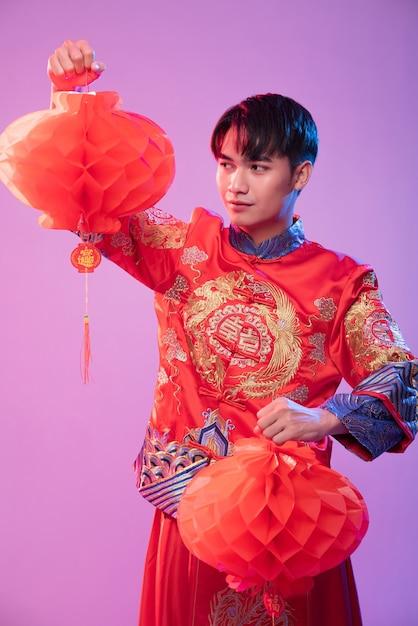 L'uomo indossa lo spettacolo cheongsam decora la lampada rossa per fare acquisti nel capodanno cinese Foto Gratuite