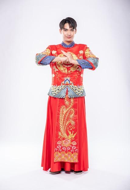 L'uomo indossa un sorriso cheongsam ed è in piedi e rispetta i clienti che vengono a fare acquisti nel capodanno cinese Foto Gratuite