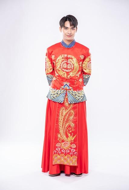 L'uomo indossa il sorriso cheongsam per accogliere lo shopping dei viaggiatori nel capodanno cinese Foto Gratuite