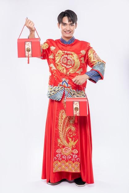 L'uomo indossa un abito cheongsam e una scarpa nera felice di ricevere una borsa rossa per sorprendere nel capodanno cinese Foto Gratuite
