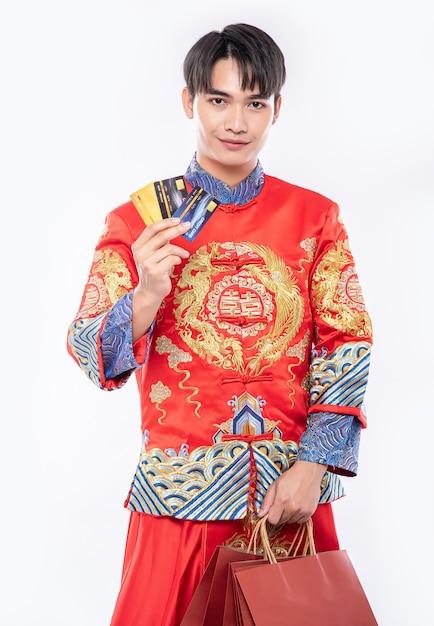 チャイナドレスを着た男性は、中国の旧正月にクレジットカードを使用することで多くのことを得る 無料写真