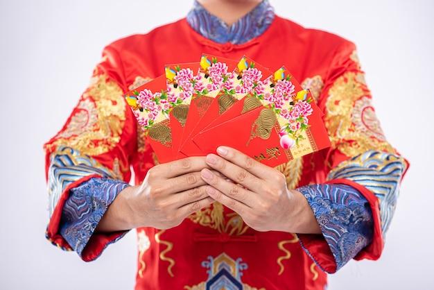 L'uomo indossa un abito cheongsam fa un regalo alla sua famiglia per essere una persona fortunata nel capodanno cinese Foto Gratuite